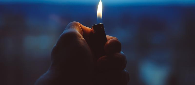 man's hand holding lighter in the dark